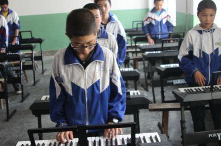 乡中学的学生大多都是从村小升入乡中学的,在村小,没有上过一节完整的音乐课,没有人告诉他们乐理知识,他们只是听着电视里的歌,听着收音机里的歌。现在能触摸电子琴,在指尖的来回拨动中,听着美妙的声音。